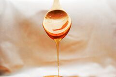 Spoon with honey draining from it Royalty Free Stock Photos