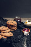 Spoon with jam near chocolate cookies and biscuits on black table background. Afternoon break time. Breakfast. Royalty Free Stock Photos