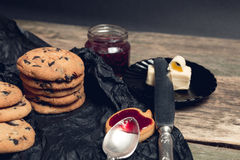 Spoon with jam near chocolate cookies and biscuits on black table background. Afternoon break time. Breakfast. Stock Images