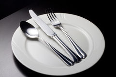 Spoon, Knife and fork on a white plate. On a dark table Stock Images