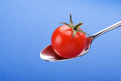 Spoon with little tomato. On a blue background Royalty Free Stock Photography
