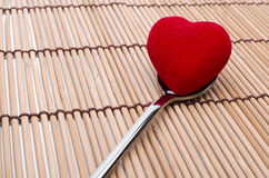A spoon of love. Red heart in a spoon on a bamboo background royalty free stock photo