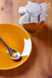 Spoon lying on  plate and standing next to a jar of honey Stock Images