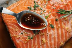 Spoon with marinade on raw salmon fillet. Closeup Stock Photo