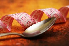 Spoon and measure tape Royalty Free Stock Images