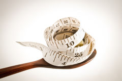 Spoon and measuring tape Royalty Free Stock Photography