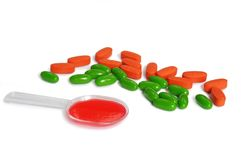 Spoon of medicine and colorfull pills Stock Image