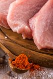 Spoon with milled pepper next to slices of raw pork meat on wooden plate Royalty Free Stock Images