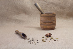 Spoon and mortar, pepper and cardamom, star anise at sacking Royalty Free Stock Photo