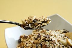 Spoon of muesli above a bowl Royalty Free Stock Photos
