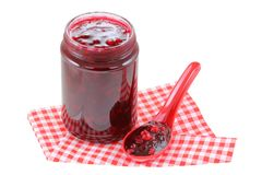 A spoon next to a jar of Cranberry jam Royalty Free Stock Photography