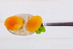 Spoon of oatmeal porridge with apricots Stock Photo