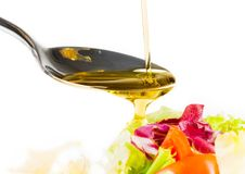 Spoon with olive oil on italian fresh salad Stock Image