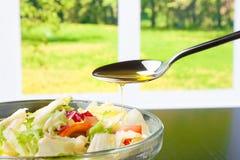 Spoon with olive oil on italian fresh salad Stock Photos