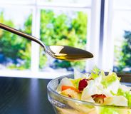 Spoon with olive oil on italian fresh salad Royalty Free Stock Image