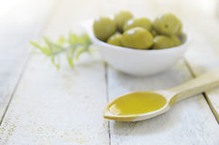 Spoon with olive oil next to some natural green olives. Scene on a wooden white table of a rustic kitchen Stock Photos