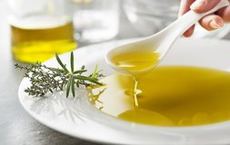 Spoon with Olive oil pouring close up stock photography