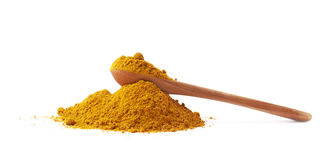 Spoon over the pile of curry powder Royalty Free Stock Photo