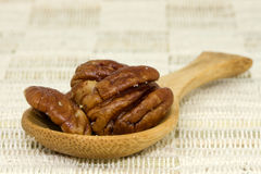 Spoon with pecan nuts Stock Photos