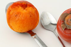 On a spoon persimmon pulp. A few persimmons on white background Royalty Free Stock Photos