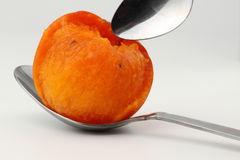 On a spoon persimmon pulp. A few persimmons on white background Stock Photo
