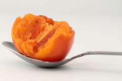 On a spoon persimmon pulp. A few persimmons on white background Royalty Free Stock Images