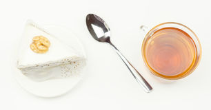 Spoon, piece of cake,  tea lying on a  surface. Spoon, piece of cake,  tea lying on a white surface Stock Image