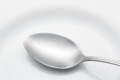 Spoon on a plate Stock Photography