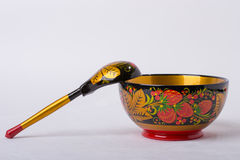 A spoon and a plate of Russian folk painting. Spoon and plate with Russian folk painting on a white background Khokhloma painting Stock Photo