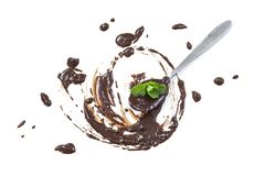 Spoon in a pool of Chocolate frame, with mint leaves, isolated on white stock photo