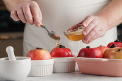 Spoon pouring honey on apple. making baked apple. Royalty Free Stock Images