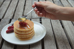Spoon pouring honey on pancakes Stock Image