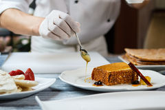 Spoon pouring honey on plate. Stock Image