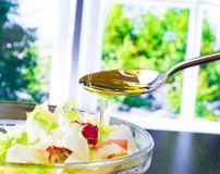 Spoon with pouring olive oil on italian fresh salad Stock Image