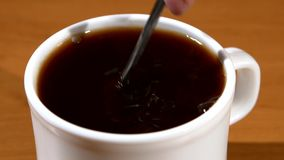 Spoon pouring sugar into a cup of coffee, wood stock video footage