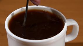 Spoon pouring sugar into a cup of coffee, wood. Silver poon pouring white sugar into a cup of black coffee, wood background, slow motion stock footage