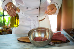 Spoon pours liquid on meat. Stock Photo