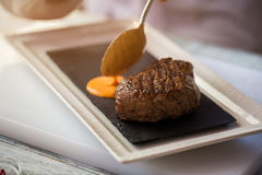 Spoon pours orange liquid. Royalty Free Stock Photo