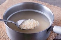 Spoon with raw rice over saucepan on wooden table royalty free stock photography