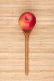 Spoon with red apple lying on the bamboo mat Royalty Free Stock Photos