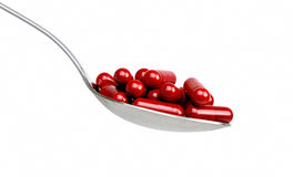 Spoon with red capsules Royalty Free Stock Images