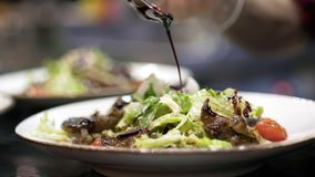 Spoon with sauce is poured over salad. Action. Closeup of aesthetic pouring jets of salad sauce by professional chef in. Restaurant stock footage