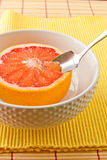 Spoon sectioning ruby red grapefruit Stock Photography