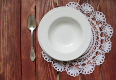 Spoon and set of dining plates on lacy napkin Royalty Free Stock Image