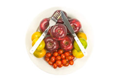 Spoon and silverware on apple, orange, tomato. In dish Royalty Free Stock Photography