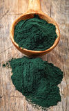 Spoon of spirulina algae powder. On old wooden table background Stock Photography