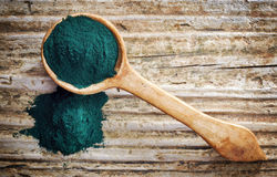Spoon of spirulina algae powder. On wooden background, top view Stock Images