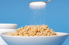 Spoon sprinkling sugar on a bowl of oat cereal on blue backgroun Stock Image