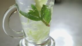 Ginger drink close up. Spoon stirring his tea with mint and lemon in a transparent glass, shot close-up stock video