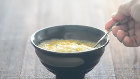 Spoon stirring and scooping rice porridge. On dining table, natural lighting background stock footage